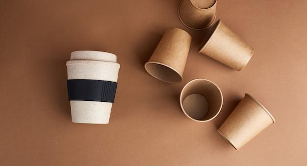 ゼロウェイストの現代的な方法。多くの使い捨て紙コップに対して1つの再利用可能な竹製のコップ。コーヒーとエコロジー。ベージュの背景