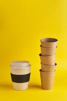 ゼロウェイストの現代的な方法。多くの使い捨て紙コップに対して1つの再利用可能な竹製のコップ。コーヒーとエコロジー。黄色の背景