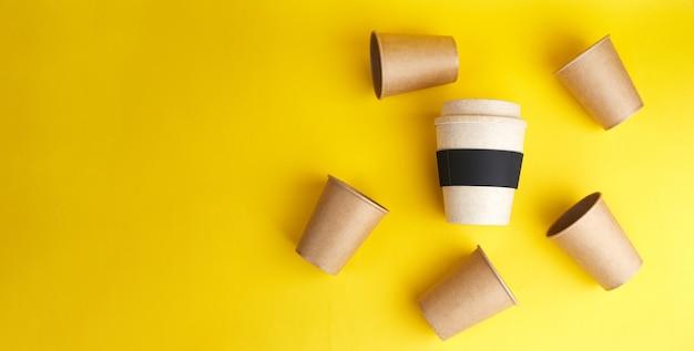 ゼロウェイストの現代的な方法。多くの使い捨て紙コップに対して1つの再利用可能な竹製のコップ。コーヒーとエコロジー。コピースペースと黄色のバナー