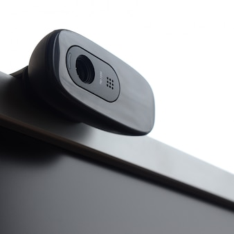 A modern web camera is installed on the body of a flat screen monitor.