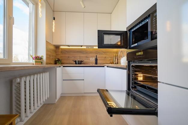 オーブンが開いたモダンな白とベージュの木製キッチンインテリア