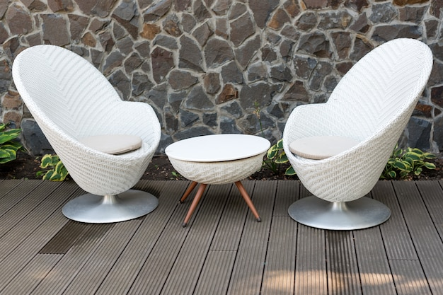 Modern white armchairs and table, modern garden furniture.