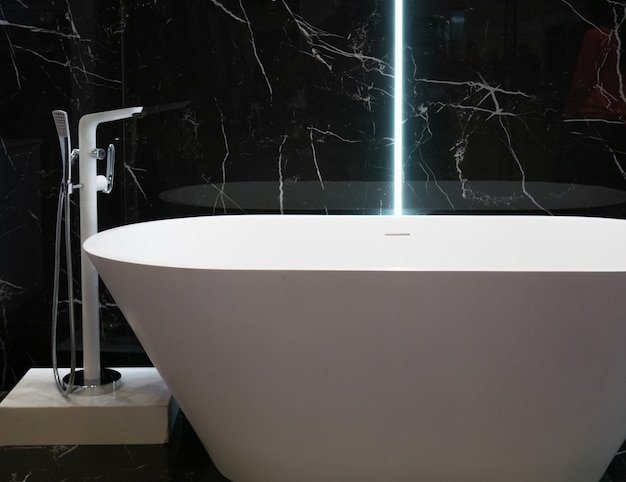 Modern white bathtub at hotel apartment with black marble wall interior design at bathroom