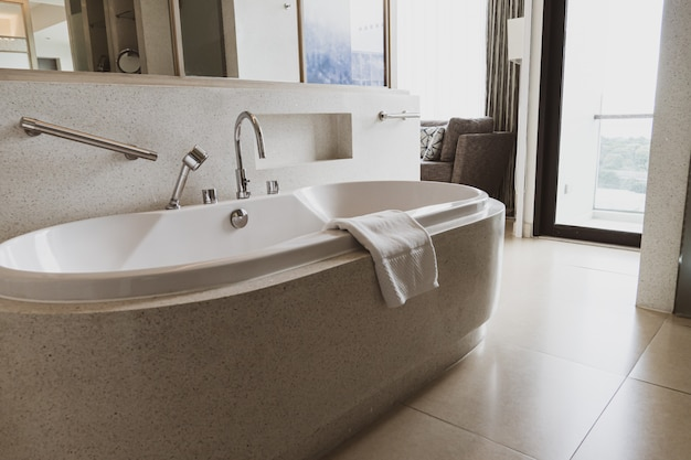 Современная белая ванна в современной ванной комнате. красивая роскошная ванна в белых тонах.
