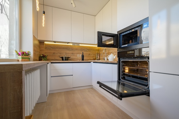 Modern white and beige wooden kitchen interior with oven opened