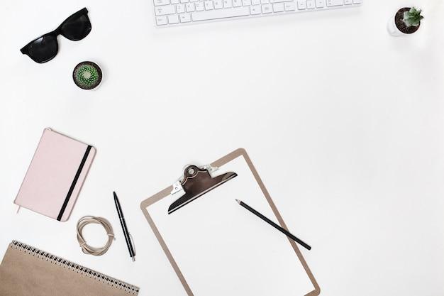 白いキーボード、フォルダータブレット、サボテン、ピンクの日記付きのモダンな白いブロガーのデスクテーブル