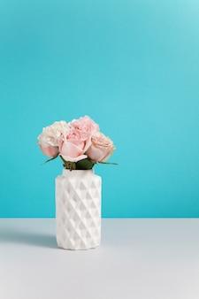 파란색 배경에 핑크 장미와 현대 화이트 세라믹 꽃병 회색 yable에 서 서. 디자인에 대 한 빈 공간을 가진 최소한의 구성입니다. 꽃이 게 개념. 인사말 카드