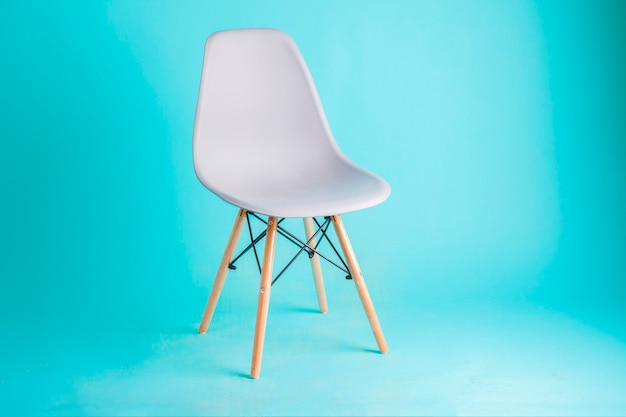 Modern white chair isolated on blue background