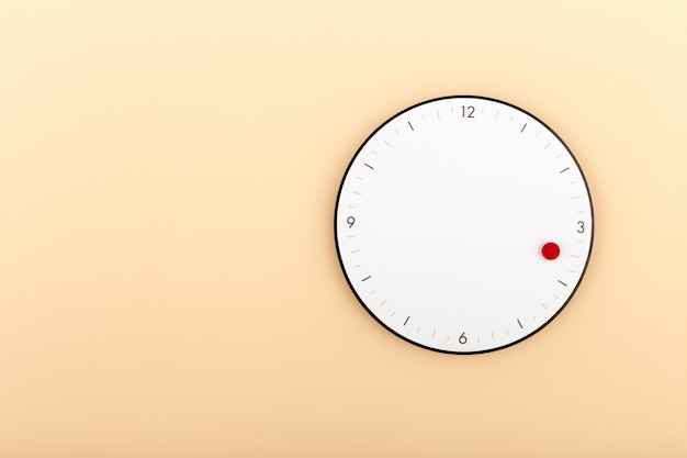 A modern white clock hanging on orange wall