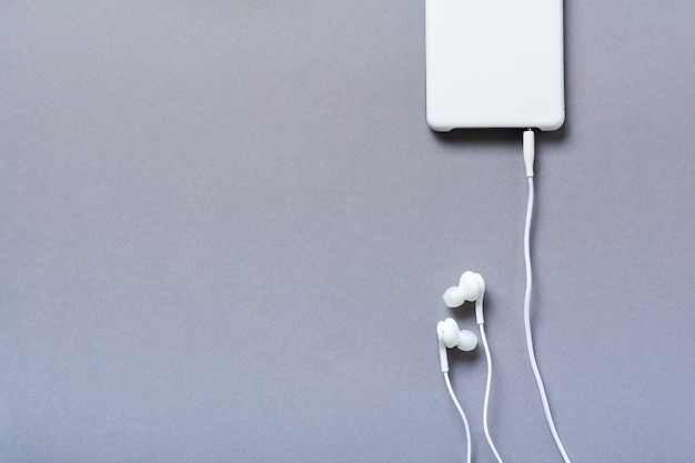 灰色の背景にモダンな白いイヤホンと携帯電話。ミニマリストスタイル。コピースペースのある上面図。