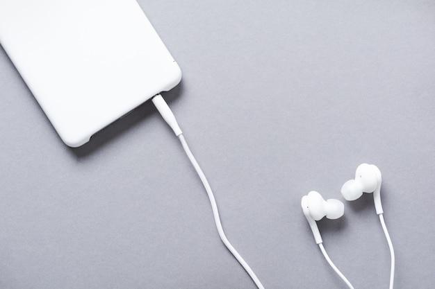 灰色のモダンな白いイヤホンと携帯電話