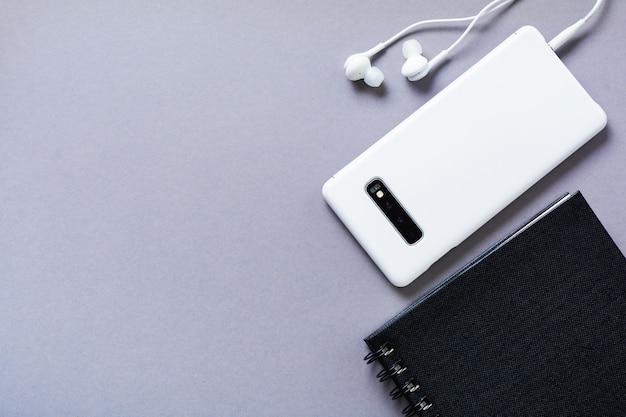 モダンな白いヘッドフォン、メモ用のメモ帳、灰色の背景の携帯電話。ミニマリストスタイル。コピースペースのある上面図。