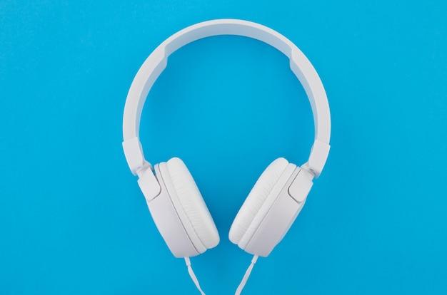 Modern white headphones on a blue