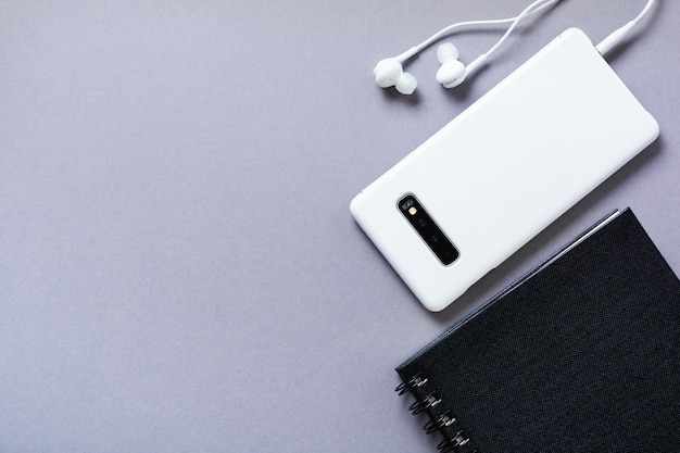 Modern white headphones, a notepad for notes and a mobile phone on a gray background. minimalist style. top view with copy space.