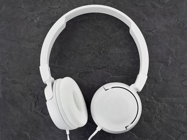Modern white headphones on a stone