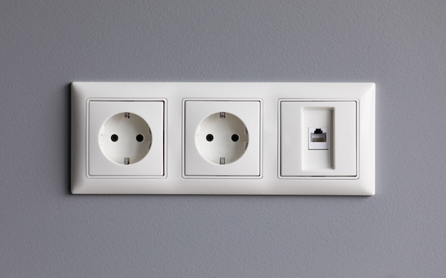 Modern white house outlet on gray wall closeup