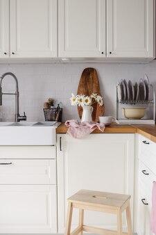 水差しやその他のキッチン用品にカモミールの花がたくさん付いたモダンな白いキッチン