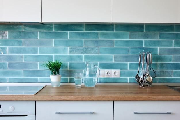 Современная белая кухня с посудой на стене из синей плитки