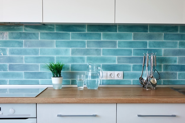 Modern white kitchen with utensils on the wall of blue tiles