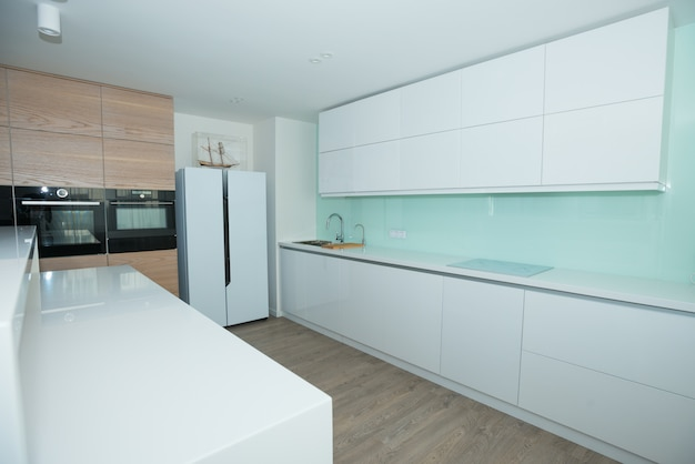 Modern white kitchen with wooden panels