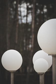 Современные белые фонари на металлической планке большие круглые фонари на городской улице