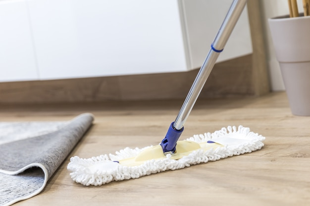 Modern white mop being used for cleaning a wooden floor