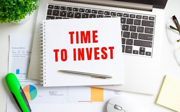 Современный белый офисный стол с ноутбуком и другими аксессуарами. блокнот с текстом время инвестировать.