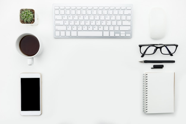 Modern white office table with computer gadgets and supplies in flat lay.