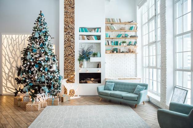 Интерьер современной белой комнаты с украшенной новогодней елкой, подарочными коробками и камином