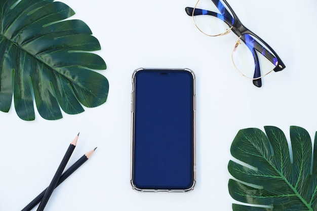 Modern white workspace and accessories, tropical leaves monstera