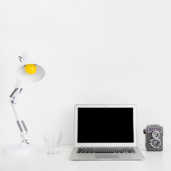 Modern white workspace with laptop and retro camera
