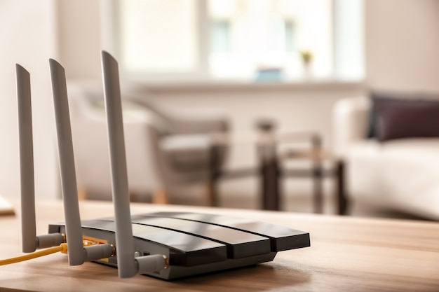 Modern wi-fi router on wooden table in room