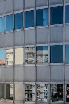 反射とモダンな窓ガラスの高層ビルの背景