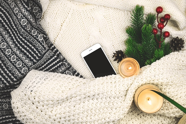 Modern winter cozy background, woolen and knitted sweater, fir branch with red berries and candles, blank smartphone. high quality photo