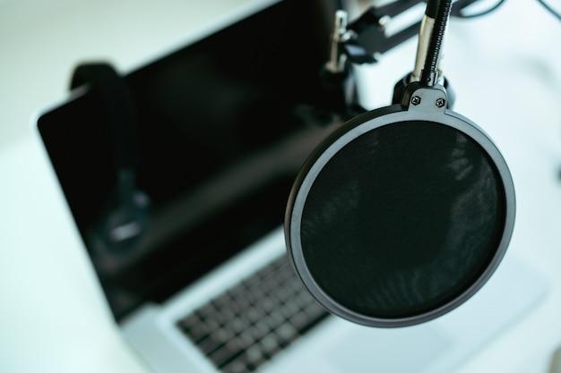 Современные проводные наушники оставлены на портативном компьютере с copyspace. наушники на персональном ноутбуке. современная студия звукозаписи и онлайн-радиостанция. аудио живое паровое оборудование.