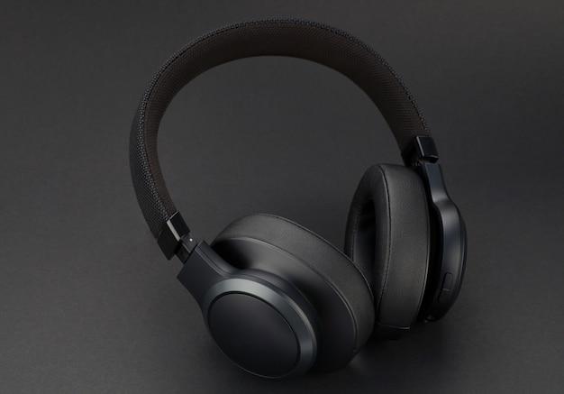 Modern wireless black headphones on a black