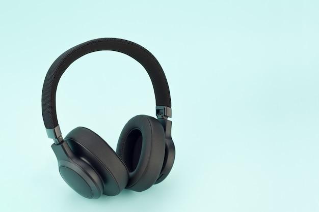 Modern wireless black headphones on a light blue