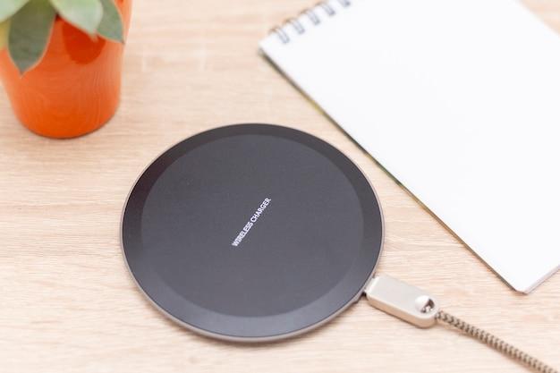 장치, 전화 및 전자 제품을위한 최신 무선 충전기. 테이블에 스마트 폰 충전기 비문 상단에 무선 충전기입니다.