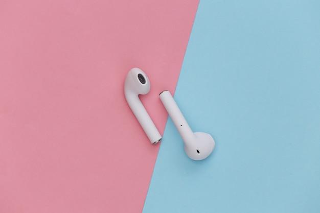 분홍색 파란색 파스텔 배경의 현대적인 무선 이어폰.