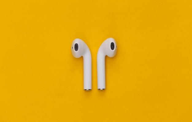 노란색 배경에 현대적인 무선 이어폰입니다.