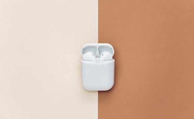 베이지색 갈색 배경에 충전 케이스가 있는 현대적인 무선 이어폰.