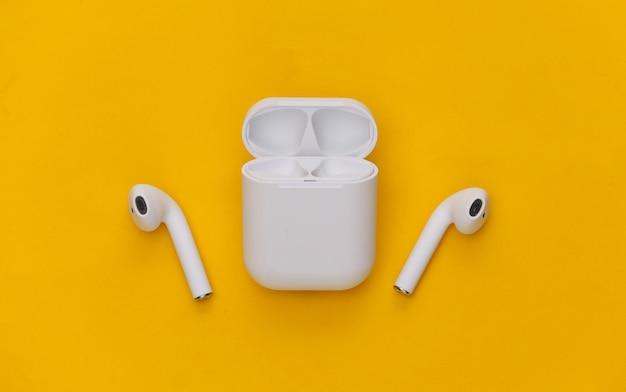 노란색 배경에 충전 케이스가 있는 현대적인 무선 이어폰.