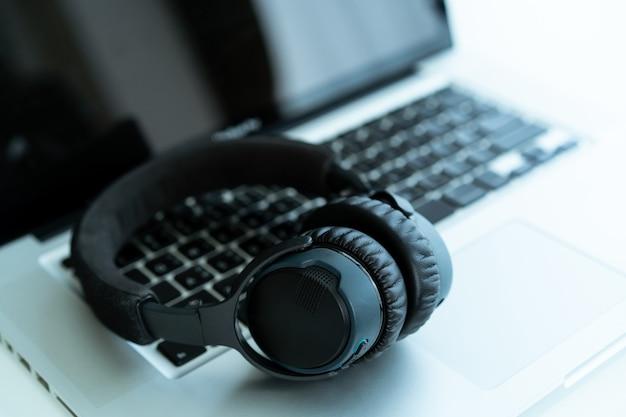 카피스페이스가 있는 노트북 컴퓨터에 현대적인 무선 헤드폰이 남아 있습니다. 개인용 노트북 컴퓨터의 헤드폰. 작업 후 휴식.
