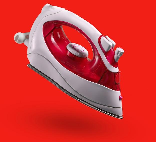 赤い背景で隔離のアイロンがけのためのモダンなワイヤレスアイロン