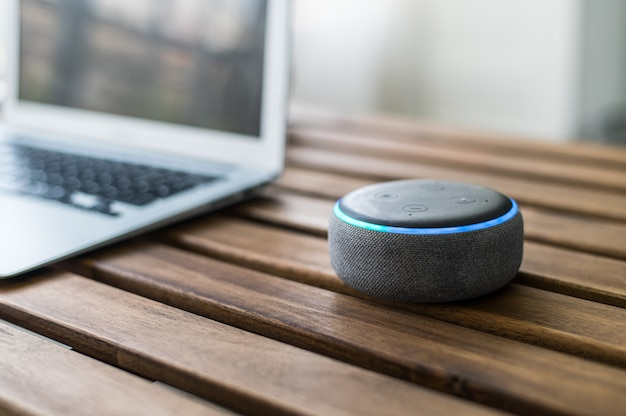 Modern wireless smart speaker placed on wooden table near blurred laptop at home