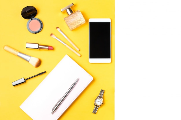 Modern woman accessories. beauty products, smartphone, note book, accessories on a pasteltable