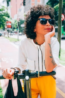Modern woman in a city with a electric scooter