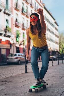 Современная женщина-героиня с маской на скейтборде. супергерой.