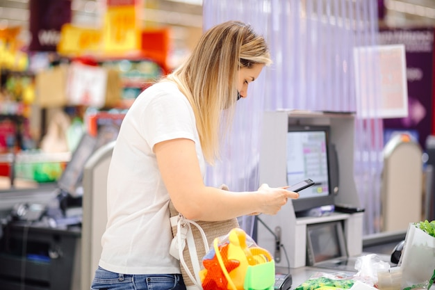 ショッピングセンターのセルフサービスチェックアウトでの個人保護マスクの現代女性は、携帯電話を使用して計算されます。セキュリティ対策と買い物。利便性とコミュニケーション。