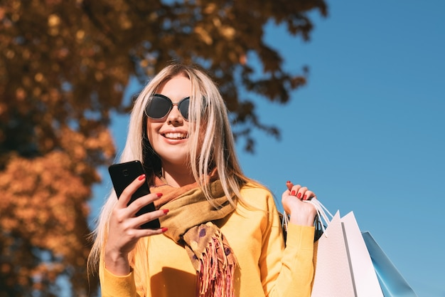 Modern woman leisure happy lady walking with shopping bags, using smartphone for chatting